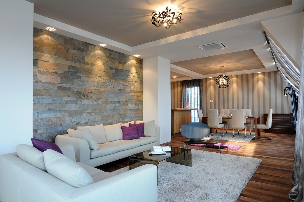 Wood floors and marbled walls touch up a contemporary look in this likely traditional looking curtains and warm colored ambiance. The simple and plain center table made of glass, plain fabric sofa set with purple cushioned pillows are among the contemporary touches in this design.