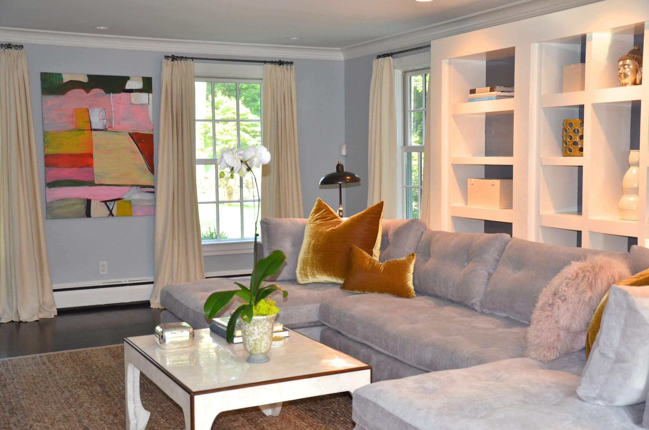 This living room features a gray sofa with white bookshelves at the back. The room is surrounded by gray walls.