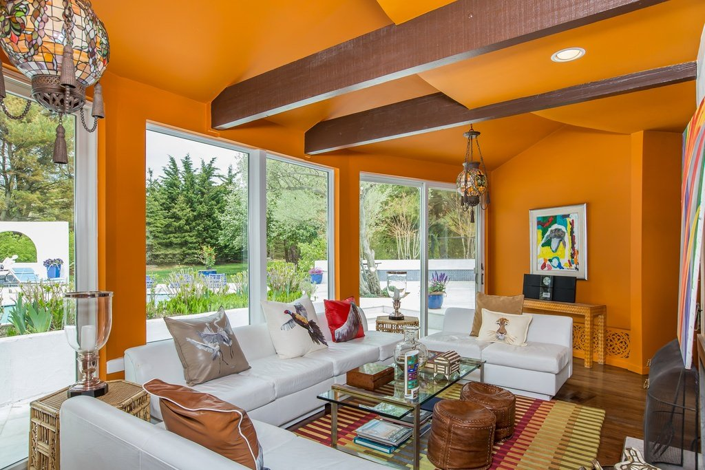 The exposed wood beams on the ceiling would normally be the attention catchers here, but not with the wall and ceiling painted in bright orange! The wall paintings, floor rug, and the hanging pendant lights creatively decorated with artsy covers all have accents of orange too. And did you notice the orange-striped wooden desk camouflaged against the wall?