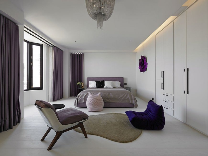 This room is characterized by minimalist design, a low bed with a lot of empty space around the white details. Modern seating choices accent the minimalist theme.
