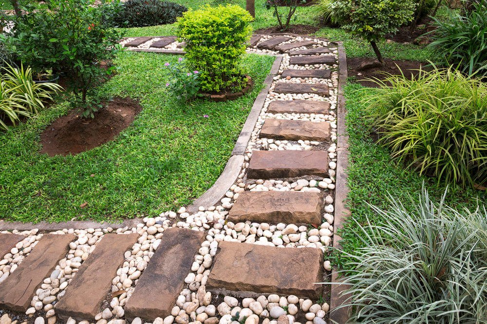 These blocks were assembled into a pathway sprinkled with white stones to fill in each of its gap while the concrete curb saves them inside the line.