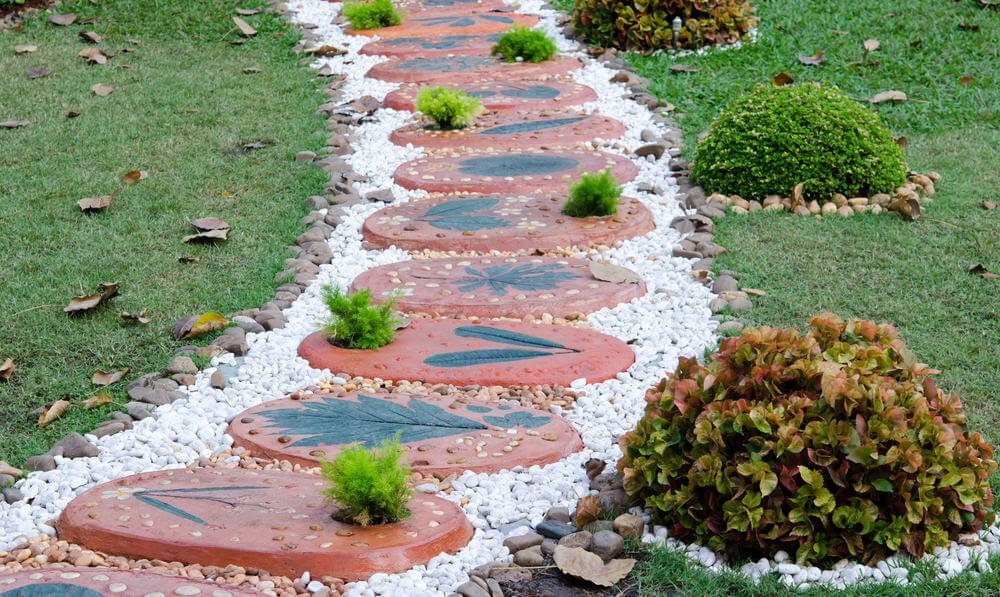These decorative oval pavers in white and brown pebbles once again steal the spotlight. The side is lined with shrubs trimmed in rounds.