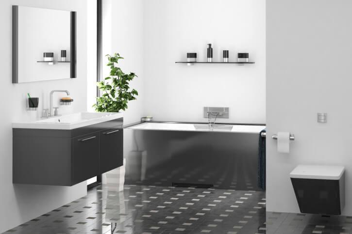A simple overhauled bathroom in grey painted walls, shimmering dark grey vanities and a elegant floor tiles and patterns.