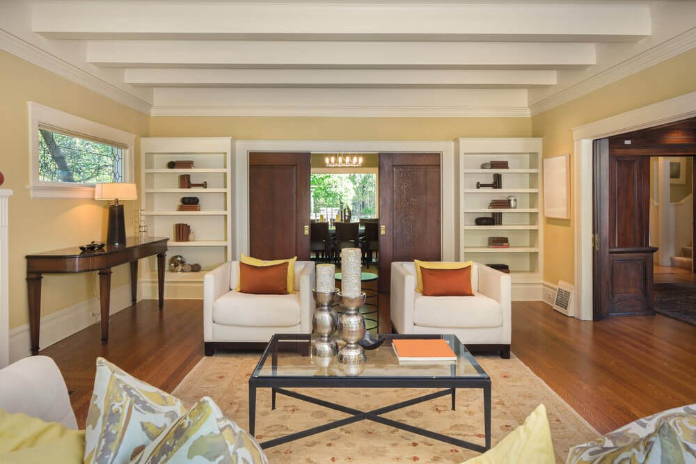 Spacious living room featuring a ceiling with beams and a pair of bookshelves on both sides of the door.