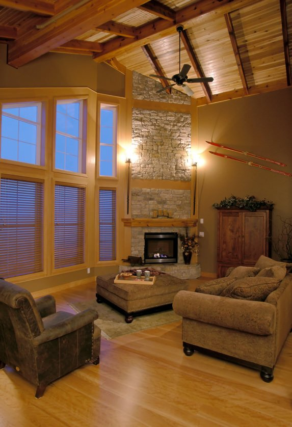 Heavy timber exposed on large windows and cathedral ceiling as well as the stone fireplace are among the examples of being a West Coast Contemporary designed living room with a touch of traditional furniture and sofa sets.