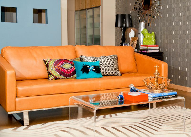 The orange leather sofa is the glamour in the spotlight of this living room. A few touches of orange can also be found on the conversation pieces atop the glass center table, like the orange tray and orange plated crown.