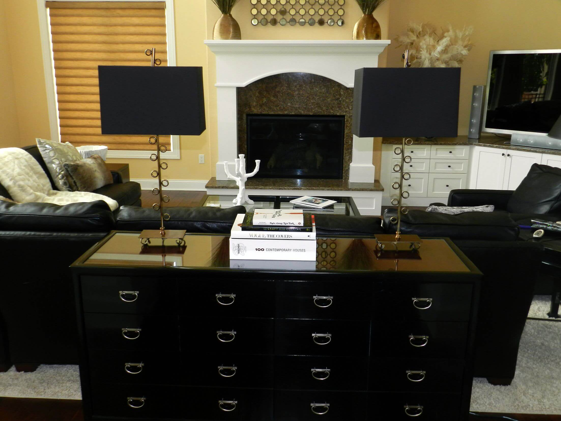 A living room featuring black leather seats and a stylish table cabinet at the back.