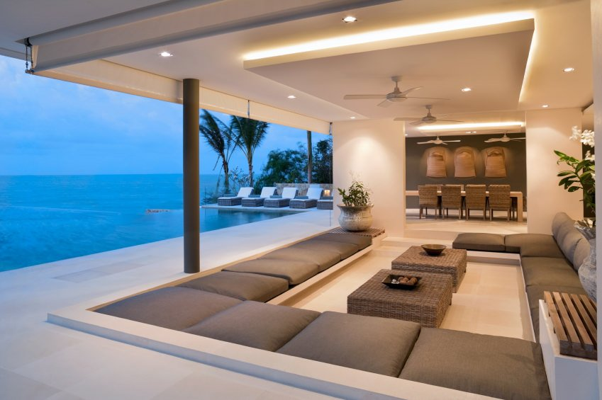 An open wall revealing rows of cushioned sofa benching around a pair of rattan center tables. While the distance is wide opening revealing the dining area.