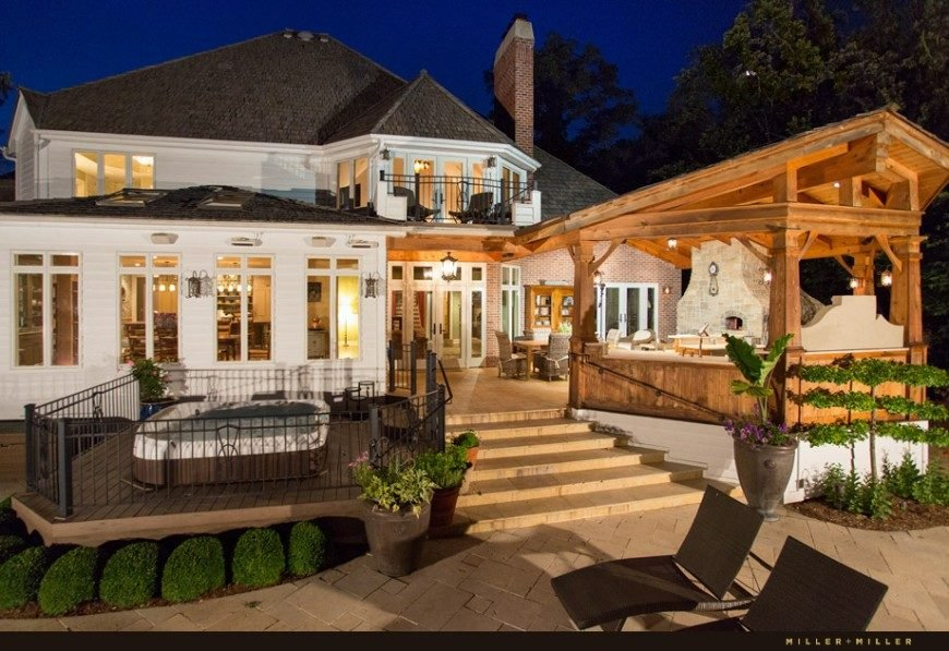 This deck complex features a large dining area, a covered kitchen area, and a lower tier with a fenced in hot tub that overlooks the swimming pool.