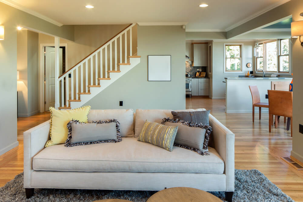 A close-up look at this living room's couch set on the gray rug covering the hardwood flooring.