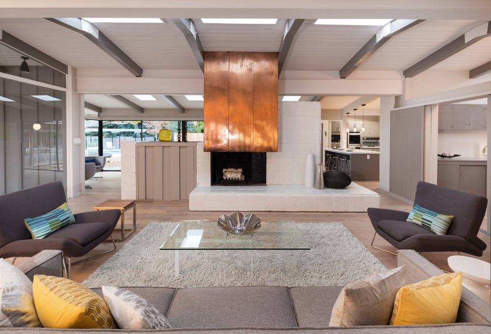 The wooden fire place top is the center attraction of this design. There are a few walls dividing the living room to the other areas. As you can see there are no other center pieces added aside from a single silver bowl mounted on the table.