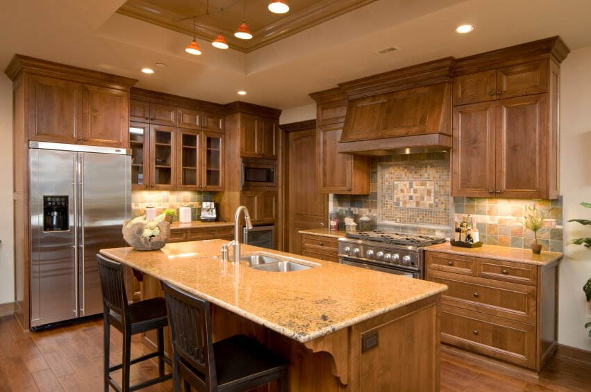 This lovely Craftsman kitchen features a deep tray ceiling, simply carved natural wood cabinetry, and natural stone tilework that includes a mosaic medallion behind the stove and range.