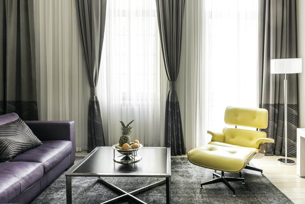 A close up look at the living space's yellow chair and classy window curtains.