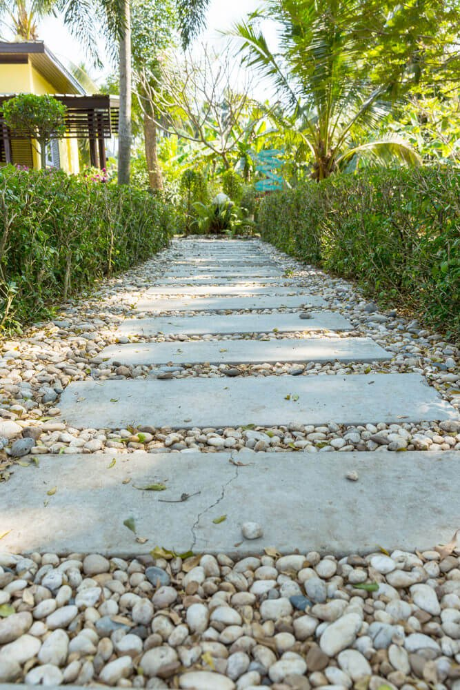 These rectangular pavers, when aligned in a row, will form a useful pathway yet when poured with white pebbles around will turn out as simple and decorative.