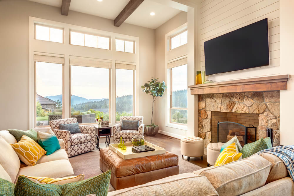 This living room features comfortable seats, a stone fireplace with a large widescreen TV on top. The room has a tall ceiling.