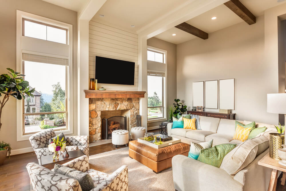 Large living room featuring hardwood floors and cream walls. It has nice seats and a fireplace with a large TV on top.