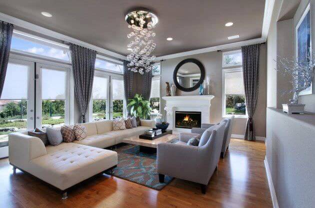 This living room features hardwood flooring and gray walls. It offers a long L-shaped sofa along with gray seats and a fireplace.