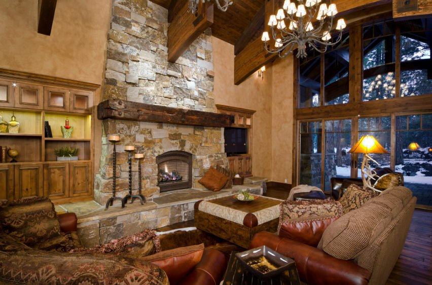 Brick stone fire place provides warmth in this mixed traditional and modern inspired chalet. It has a few lampshades and candle stands with a few comfortable sofa throws with pillows.