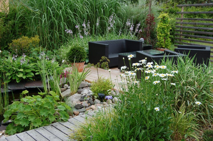 A wood pallet pathway ornamented with mini fish pond, leading its way towards an outdoor patio.