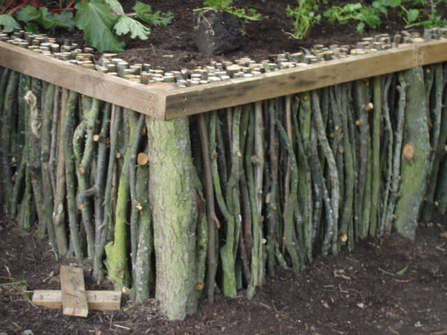 For a unique take on a raised bed that is cheap, what better way to come across the materials than by foraging in the woods for branches and logs? Talk about recycling!