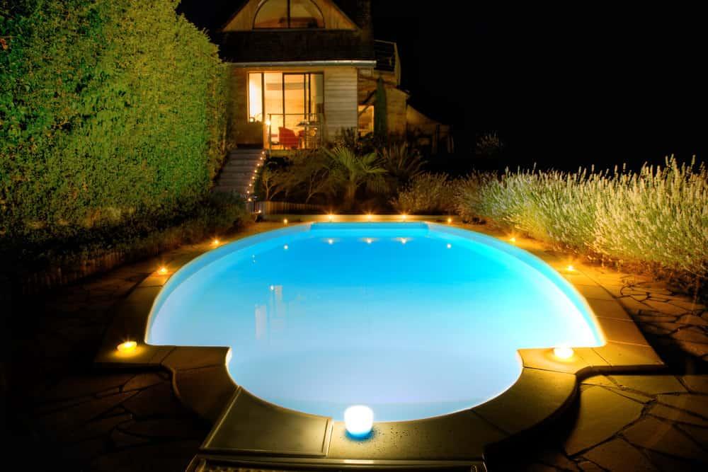 Outdoor inground pool lit up at night