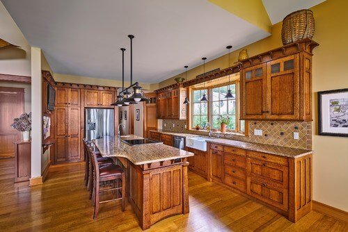 While we still see stainless steel appliances, the rest of the metal in the kitchen looks like cast iron. A few small details, like handwoven baskets, draw attention to the high ceilings.
