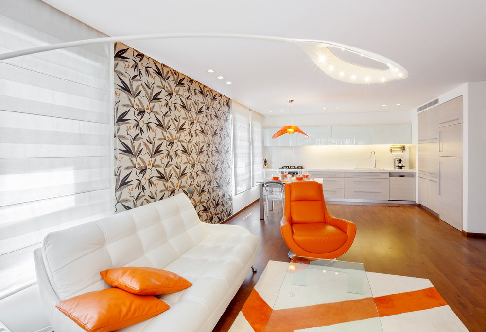 Aside from the orange accents in the living area, the dining area behind it stuns with a chic and stylish orange pendant light and an orange dining set on the dining table.