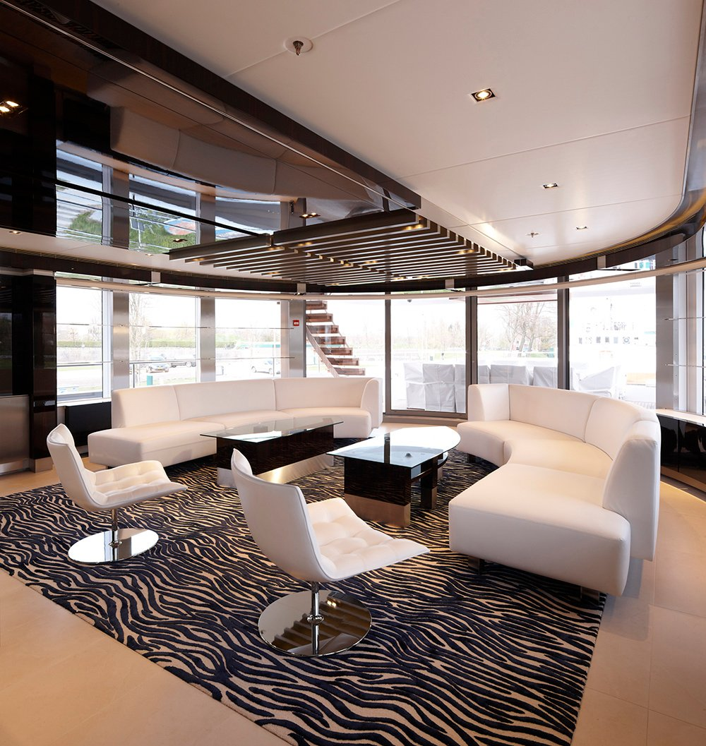 Zebra like patterns on the floor rug is enticing, giving the minimalist design slight details. No ornamentation other than that are added so that the focus within the contemporary look concentrates on geometrical figures starting from the glass center tables and arched white and cream sofa. There is also a combination of matte and glossy surfaces, which can be seen on the flooring and ceiling.