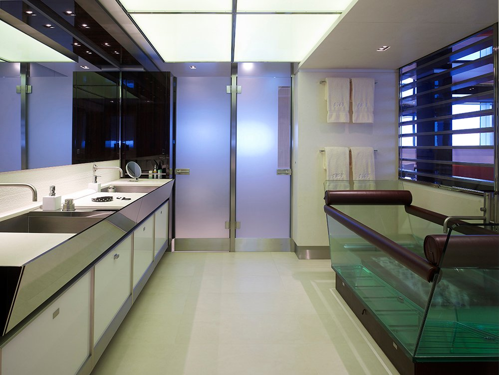 The bathroom is overviewing the suite. Inside is a unique and fab leather and glass bath tub and gleaming surfaces starting from the door and counter steel outlines, extra wide mirrors and bright lighted ceiling.