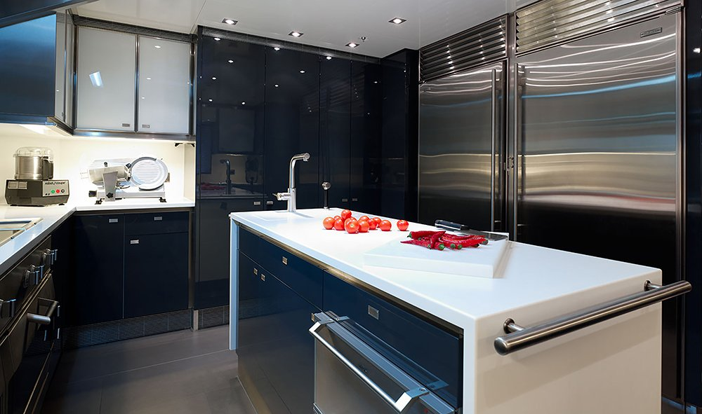 A black shaded steel kitchen with complete set of cook wares and tools. Glowing with the lights, the glossy surfaces in this area are contrasted with the matte finish flooring. The white granite counter is installed with a conventional oven behind.