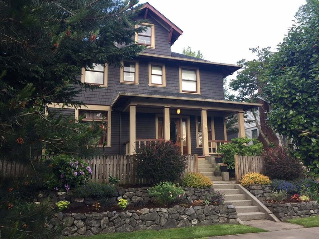 Brown shingle style foursquare with partial porch. This has a cabin look and feel to it.