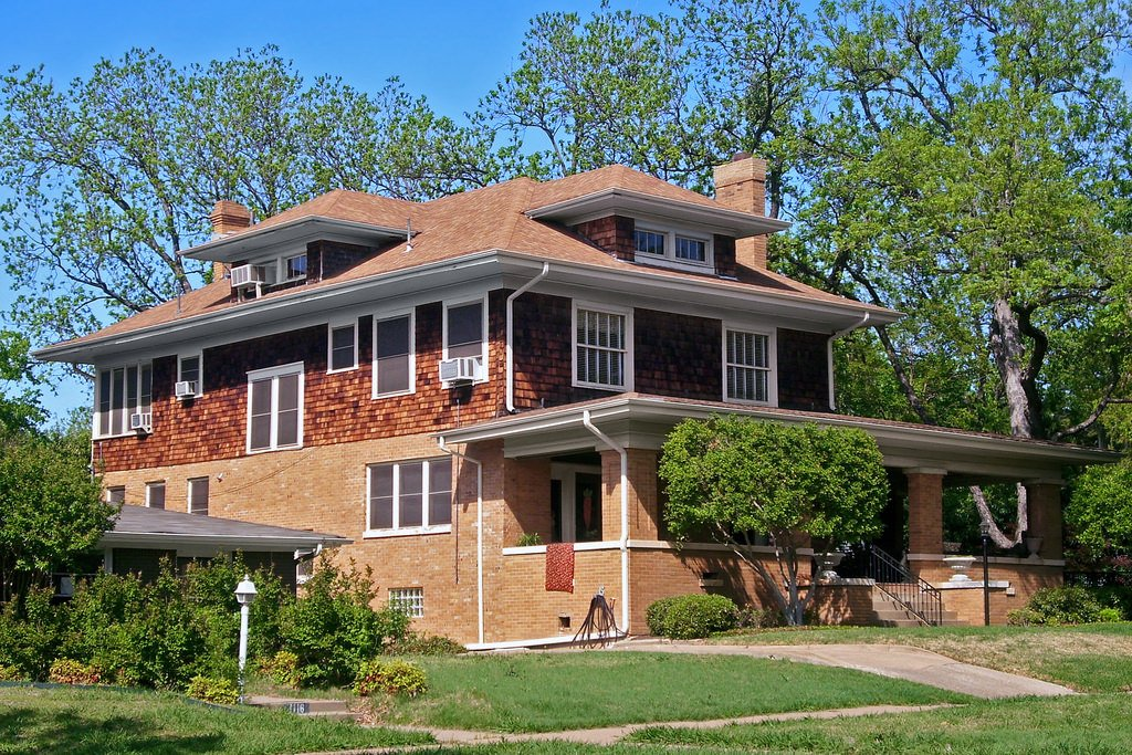 Large foursquare home with brick and wood shingle exterior. The porch is particularly large on this home.