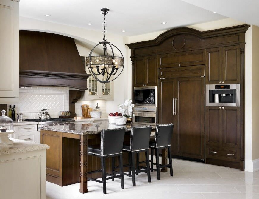 Stately kitchen design with custom dark wood pantry and stove hood as well as double stainless steel wall oven.