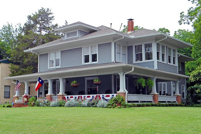 Massive gray and white foursquare home on large lot with huge porch.