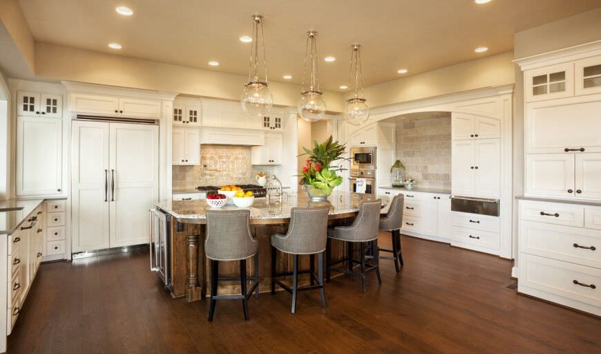 Elegant white kitchen with large diner-style island. The Double wall oven is centrally located in the corner of the kitchen and offers plenty of counterspace close to it which is a nice touch.