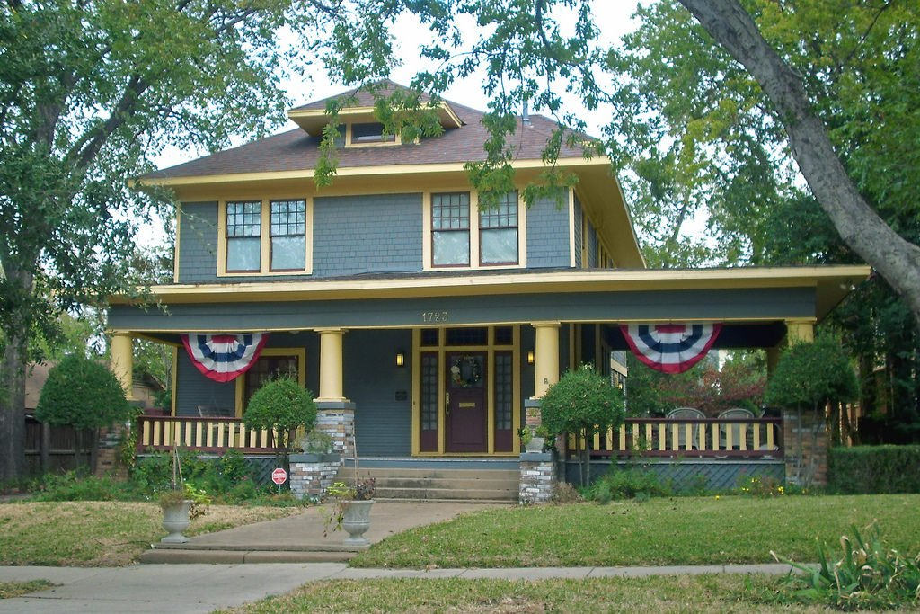 Foursquare with interesting porch that extends to the side of the home creating a large covered patio area.