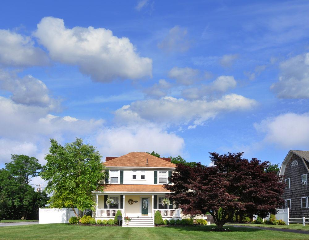White foursquare home in rural setting.