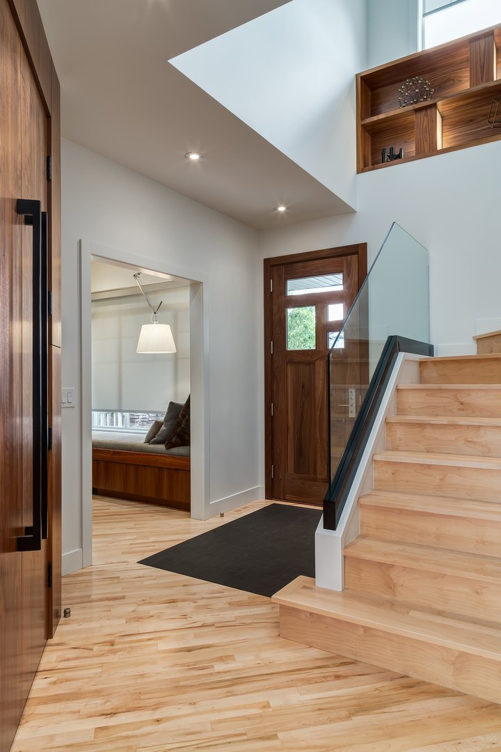 Dark wooden door with glass panels contrasts the entryway's light hardwood flooring wrapped in a black rug.
