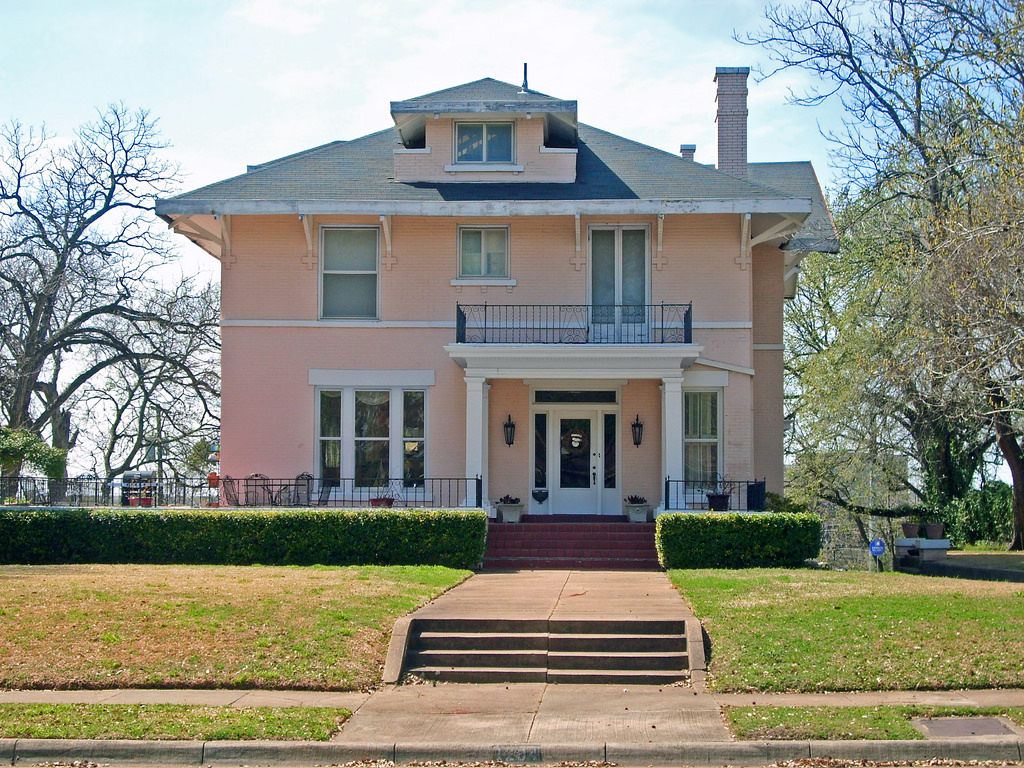 Large pink foursquare home with small porch.