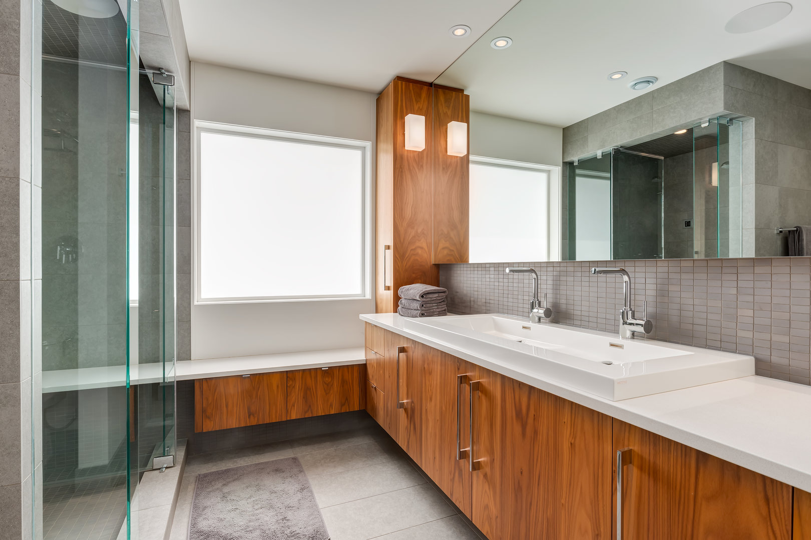 Dual sinks with plenty of counter space is backed with small brick-like grey tiles.