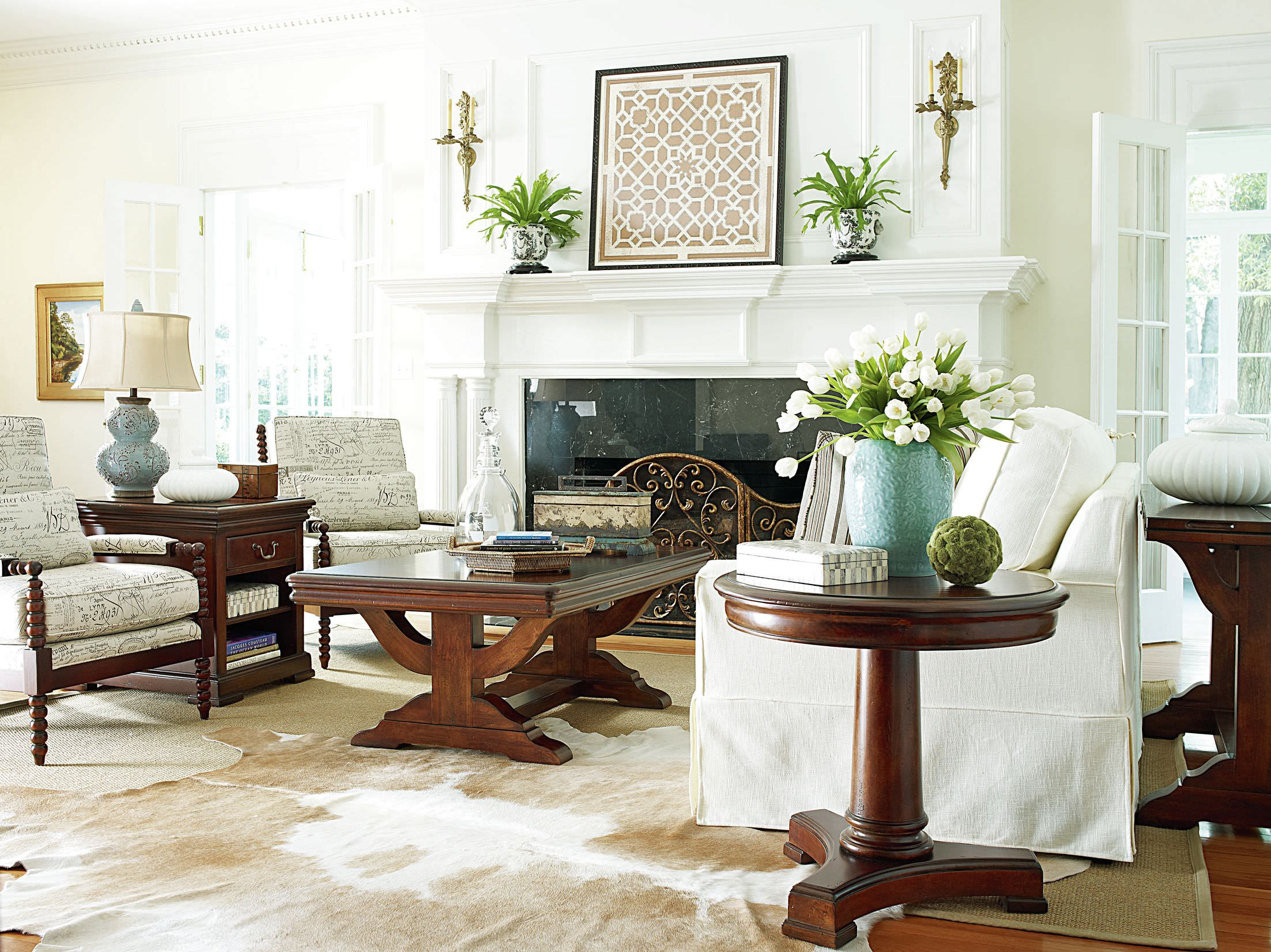 Elegantly carved hardwood furniture dominates the living room, but the white covered sofa highlights it. Together with the walls and ceiling, it reflects a bright atmosphere in the living area.