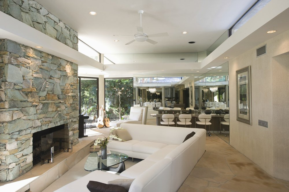 The white angled sectional sofa facing the stone fireplace is neat and sleek. It adds a nice spacing and tone to the modern minimalist design of the open space.