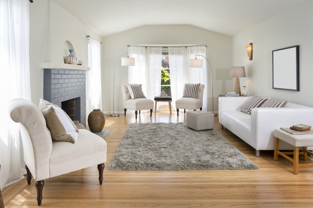 Simplicity itself: a plain sofa resting against the white wall and some matching cushioned seats at the windows.