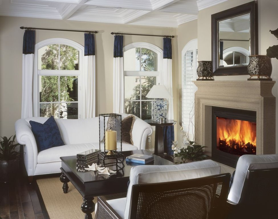 A white sofa set in an old fashioned living room. The old school appearance is due to the decoration accents on top of the carved wooden center table, corner desk and fireplace panel.