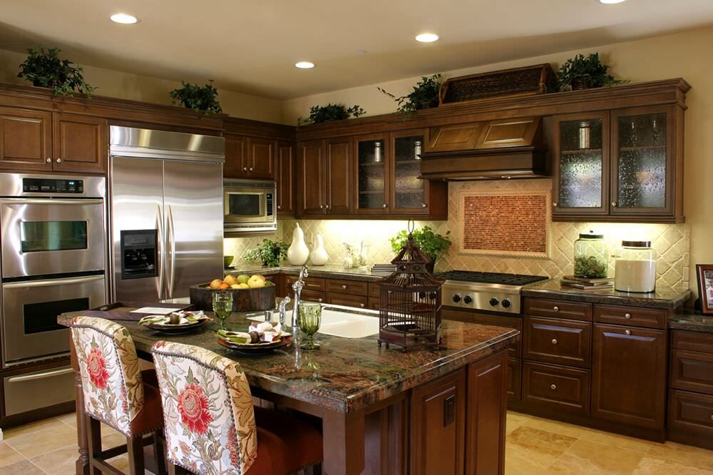 Dark kitchen design with stainless double wall oven next to stainless refrigerator.