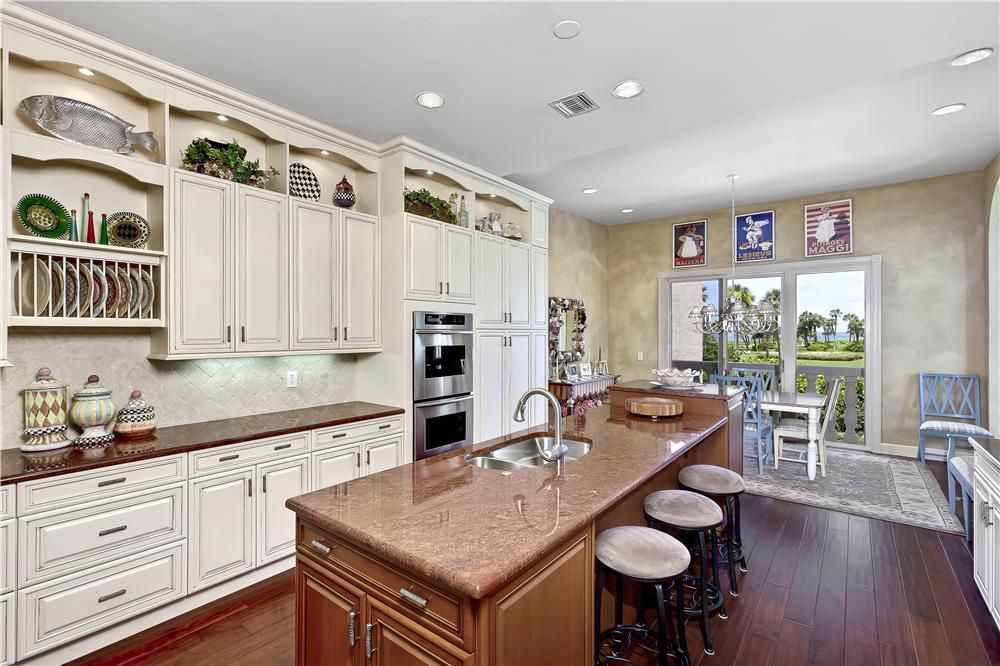Traditional kitchen design with double wall oven close to the sink and plenty of counter space next to it.