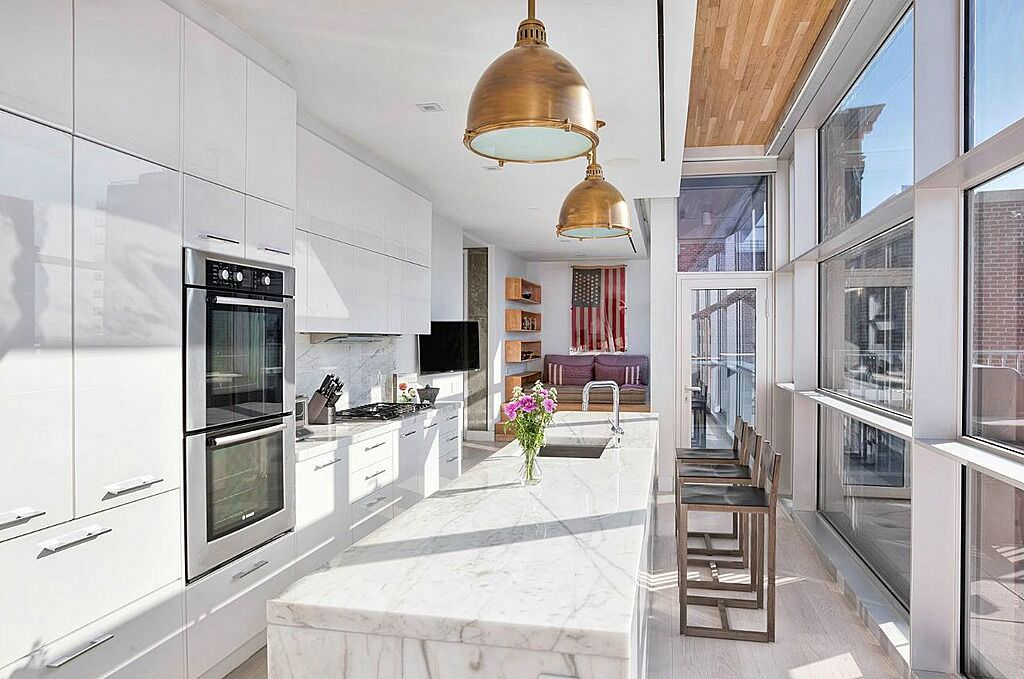 Light-filled modern kitchen with floor-to-ceiling windows and a double wall oven.