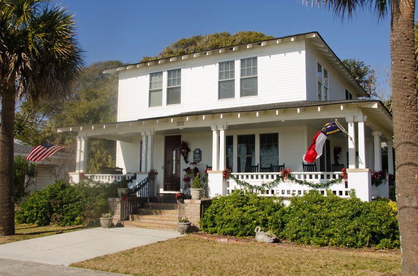 Very plain white American foursquare home with porch that wraps around the side.