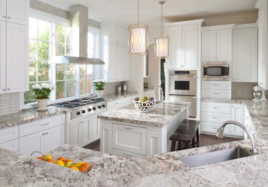 Magnificent white kitchen with double stainless steel wall oven.