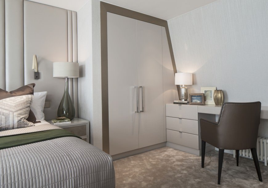 The design in this smaller primary bedroom is very smart using space to create a terrific matching built-in wardrobe/closet area.